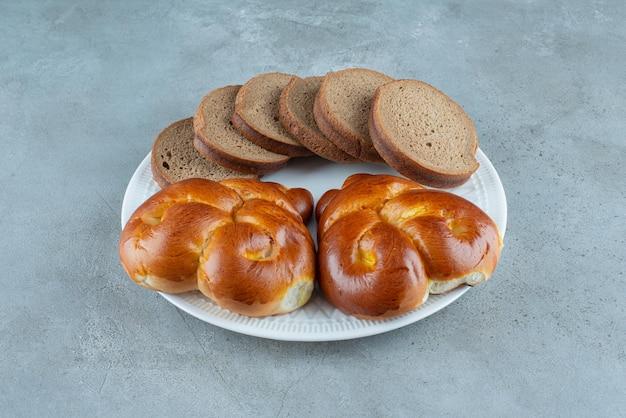Słodkie ciasto i kromki chleba na białym talerzu.