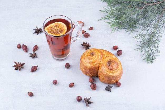 Słodkie ciasto i szklanka herbaty z owocami dzikiej róży i goździkami.