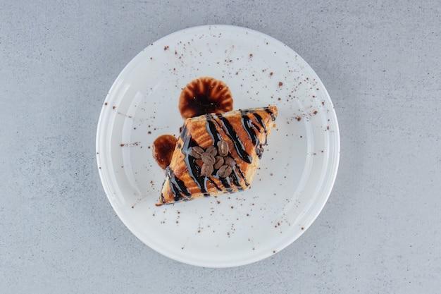 Słodkie ciasto ozdobione czekoladą na białym talerzu