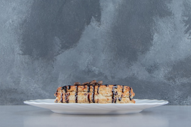 Słodkie ciasto ozdobione syropem czekoladowym na białym talerzu