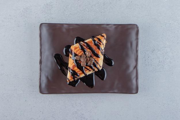 Słodkie ciasto udekorowane czekoladą na ciemnym talerzu