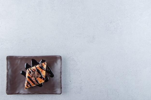 Słodkie ciasto udekorowane czekoladą ułożone na ciemnym talerzu. zdjęcie wysokiej jakości