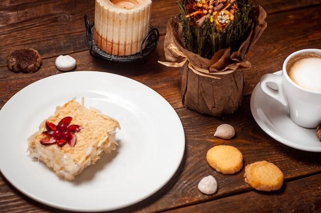 Słodkie ciasto z filiżanką kawy na drewnianym stole