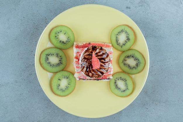 Słodkie ciasto z kawałkami kiwi na zielonym talerzu.