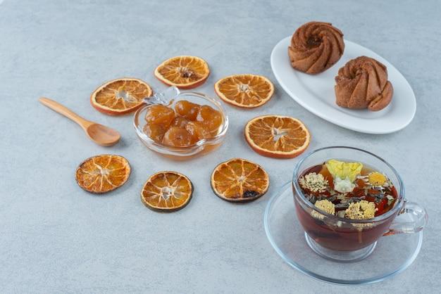 Słodkie ciasto z suszoną pomarańczą i filiżanką herbaty ziołowej na marmurowym tle. wysokiej jakości zdjęcie