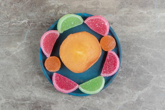 Słodkie cukierki do ciasta i marmolady na niebieskim talerzu