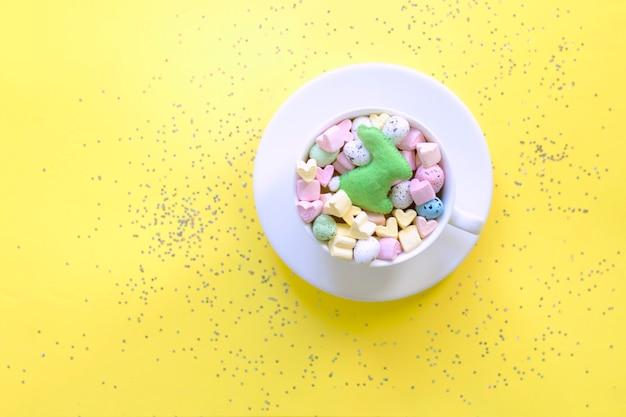 Słodkie cukierki i pianki w filiżance na żółtym tle, widok z góry. koncepcja wiosny, wielkanocy, stylu życia.