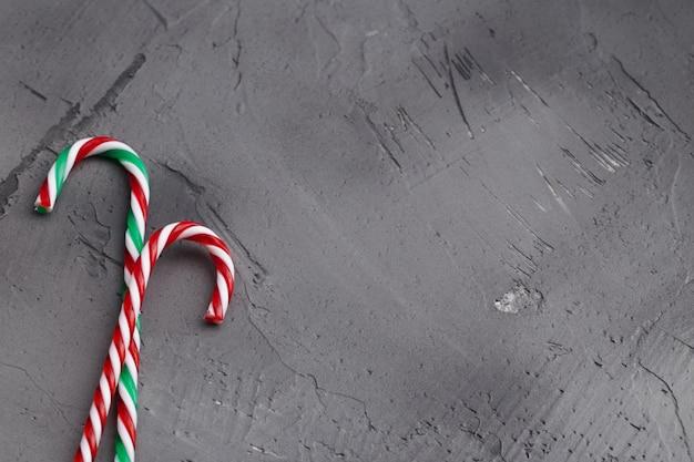 Słodkie cukierki laski na betonowym szarym tle. miejsce na tekst z płaskim layem.