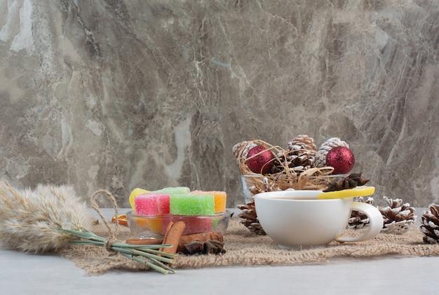 Słodkie cukierki ze smaczną filiżanką herbaty na worze. wysokiej jakości zdjęcie