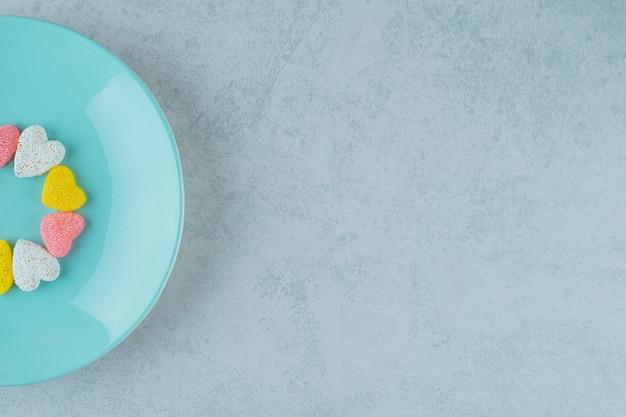Słodkie cukierkowe serca walentynkowe w niebieskim talerzu na białej powierzchni