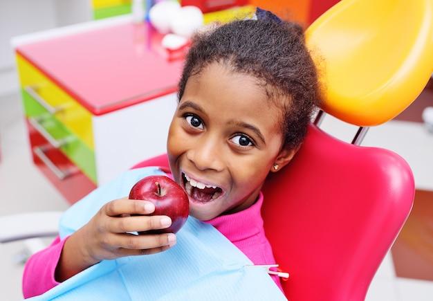 Słodkie czarne african american dziewczyna dziecko uśmiecha się i jeść dojrzałe czerwone jabłko siedzi na czerwonym fotelu dentystycznym