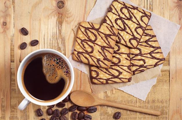 Słodkie czekoladowe ciasteczka z filiżanką kawy na śniadanie na starym stole z góry