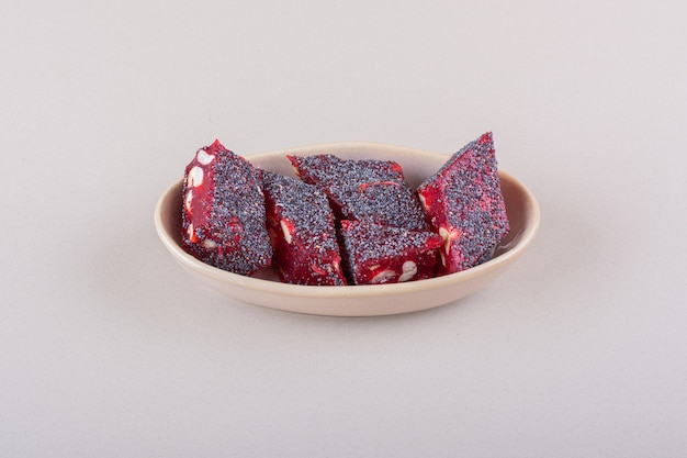 Słodkie czerwone cukierki z orzechami w beżowej misce na białej powierzchni. wysokiej jakości zdjęcie