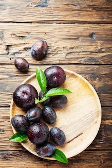 Słodkie czerwone śliwki na drewnianym stole