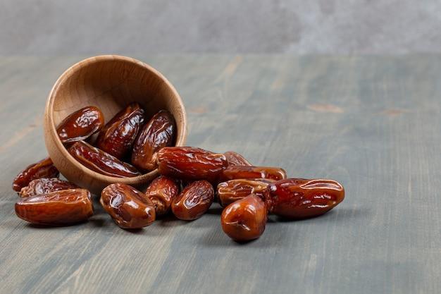 Słodkie daktyle z drewnianej miski na marmurowej powierzchni