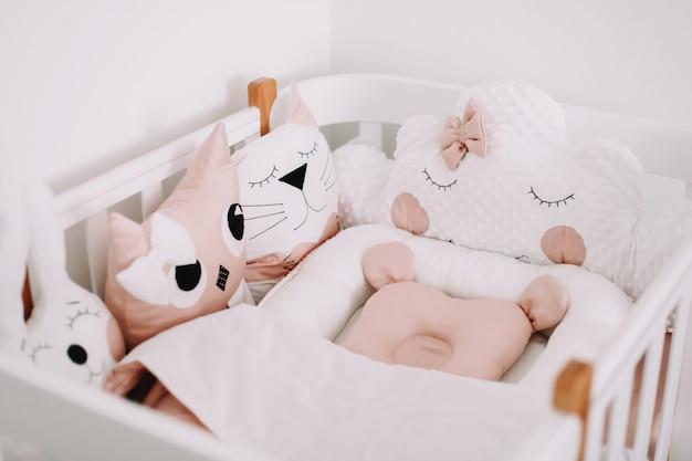 Słodkie dekoracje do pokoju dziecięcego stylowe wnętrze pokoju dziecięcego z wygodnym łóżeczkiem i zabawnymi różowymi poduszkami dekoracyjnymi
