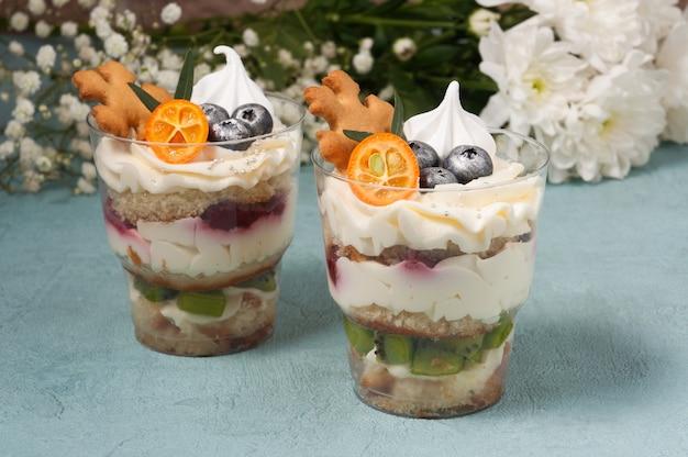 Słodkie desery w plastikowych kubeczkach ze śmietaną i czekoladą