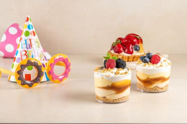 Słodkie desery ze świeżymi jagodami i urodzinową czapką na jasnej powierzchni.