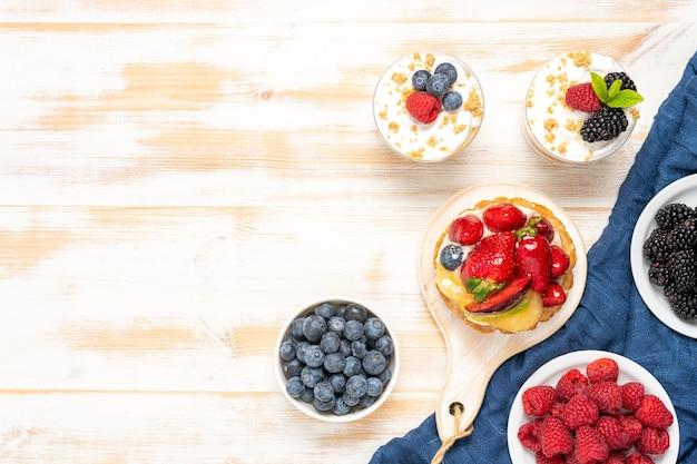 Słodkie desery ze świeżymi jagodami na drewnianym tle.