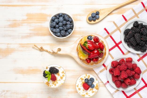 Słodkie desery ze świeżymi jagodami na powierzchni drewnianych
