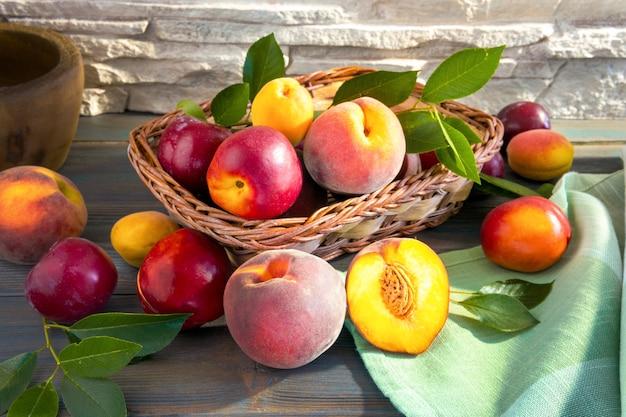 Słodkie dojrzałe soczyste owoce, brzoskwinie, śliwki, pigwa, morele z zielonymi liśćmi w koszu na ciemnym drewnianym tle na desce do krojenia