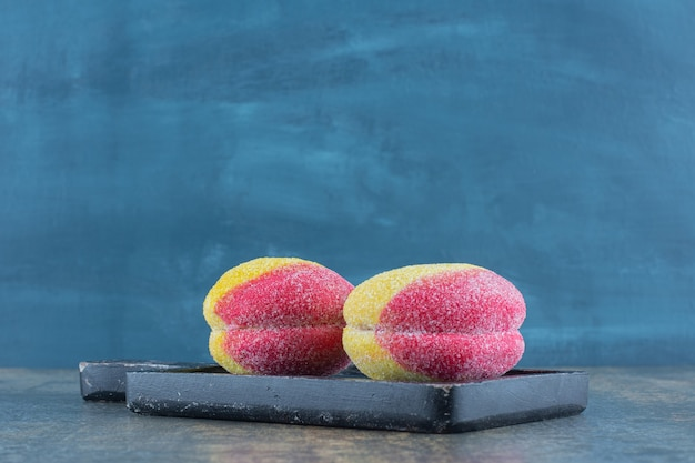 Słodkie domowe ciasteczka w kształcie brzoskwini na drewnianej desce, na marmurowej powierzchni.