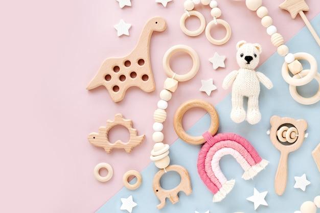 Słodkie drewniane zabawki dla dzieci na różowym i jasnoniebieskim tle.