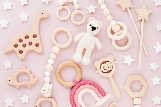 Słodkie drewniane zabawki dla dzieci na różowym tle. dzianinowy miś, tęcza, zabawka dinozaur, koraliki i gwiazdki.