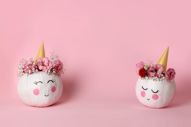 Słodkie dynie z halloweenowym makijażem na różowym tle