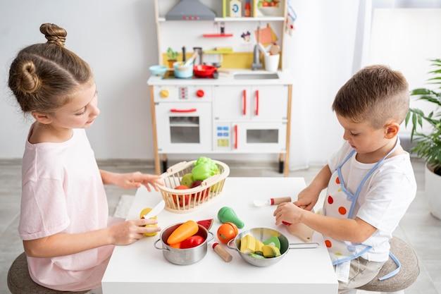 Słodkie dzieci bawiące się grą w gotowanie