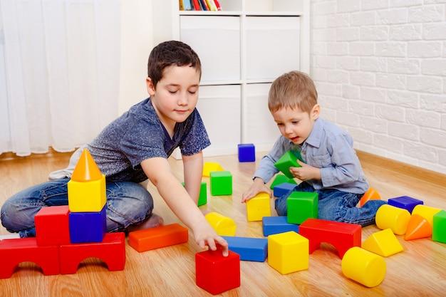 Słodkie dzieci bawiące się konstruktorem na podłodze w domu. dzieci w wieku przedszkolnym zabawy. żłobek, rozwój dzieci. na podłodze kolorowe plastikowe klocki.