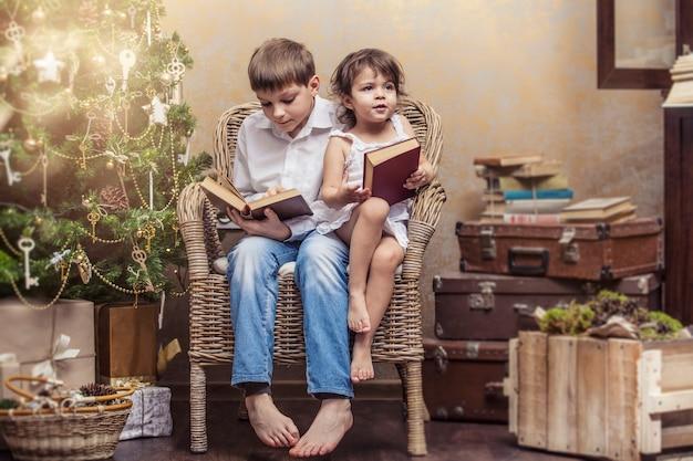 Słodkie dzieci chłopiec i dziewczynka na krześle czytając książkę w świątecznym wnętrzu retro