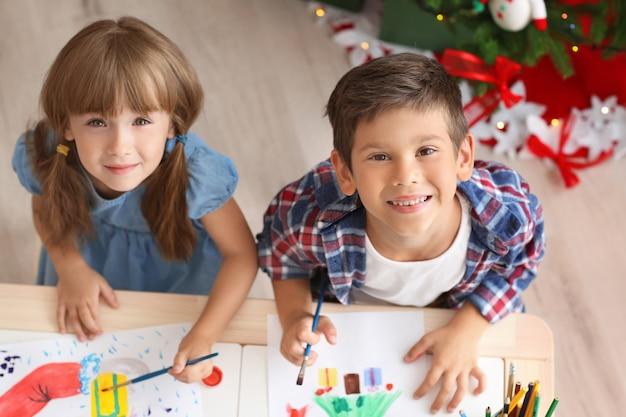 Słodkie dzieci malują świąteczne obrazki przy stole