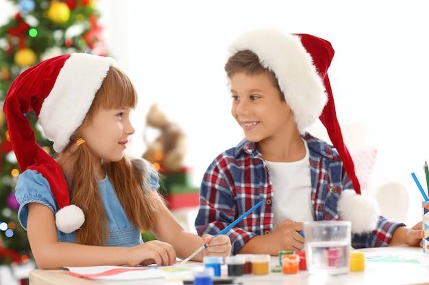 Słodkie dzieci malują zdjęcia na boże narodzenie przy stole