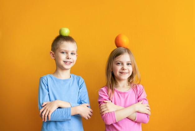 Słodkie dzieci na pomarańczowej ścianie z owocowymi zabawami, wkładają głowy i śmieją się
