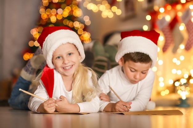 Słodkie dzieci piszą list do świętego mikołaja w pokoju urządzonym na boże narodzenie