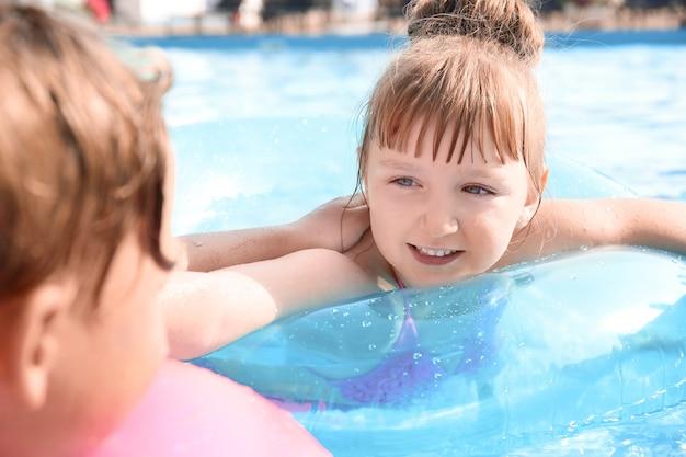 Słodkie dzieci pływają w basenie w letni dzień?