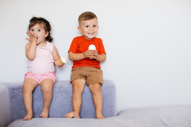 Słodkie dzieci siedzące i cieszące się lodami