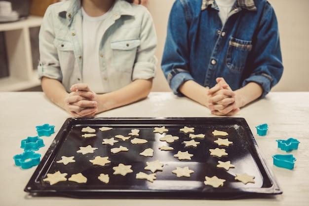 Słodkie dzieci układanie ciasteczek na blasze.