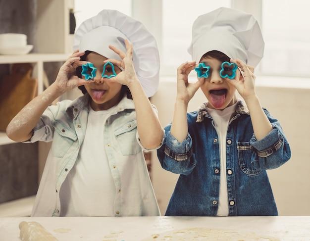 Słodkie dzieci w czapkach szefa kuchni bawią się ciasteczkami.