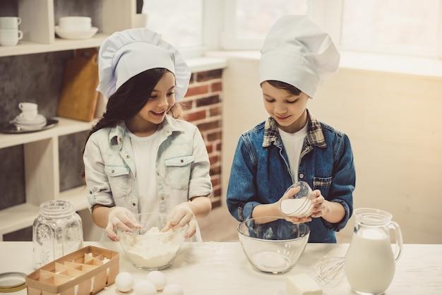 Słodkie dzieci w czapkach szefa kuchni przygotowują ciasto.