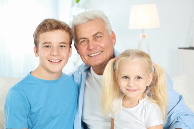 Słodkie dzieci z dziadkiem siedzi na kanapie w salonie