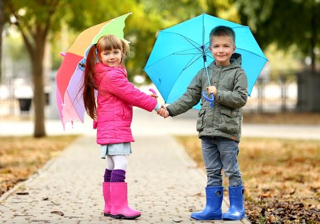 Słodkie dzieci z parasolami w parku