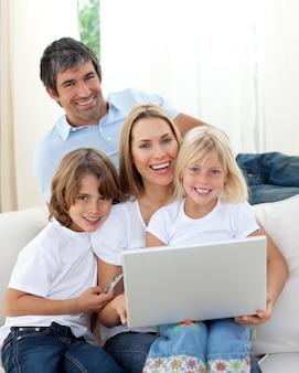 Słodkie dzieci z rodzicami za pomocą laptopa