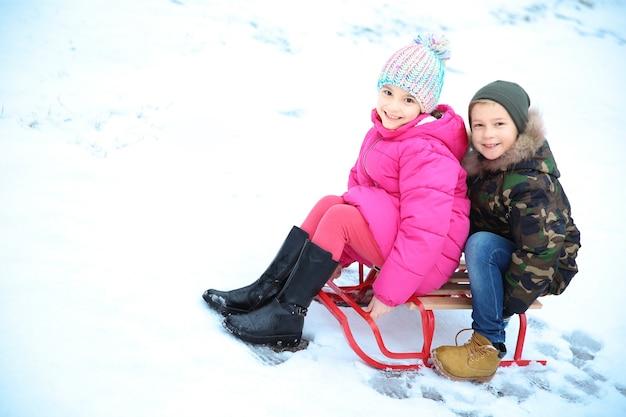 Słodkie dzieci z saniami w zaśnieżonym parku na ferie zimowe