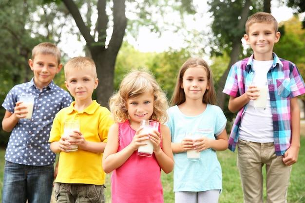 Słodkie dzieci ze szklankami mleka w parku