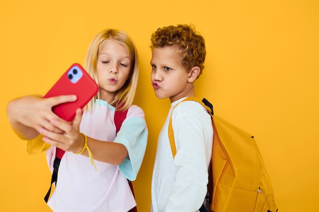 Słodkie dzieci ze szkolnymi plecakami telefon rozrywka koncepcja edukacji komunikacyjnej studio