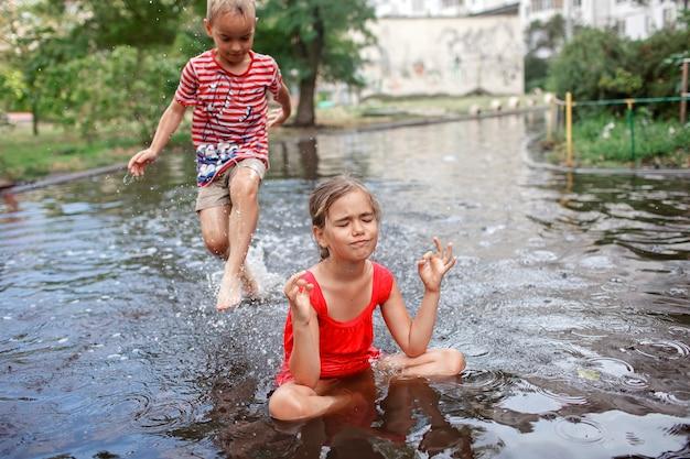 Słodkie dzieciaki skaczą i pływają w kałużach po ciepłym letnim deszczu szczęśliwe dzieciństwo