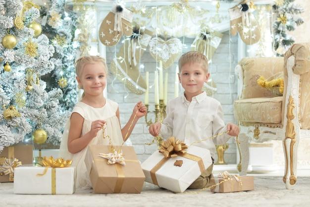 Słodkie dzieciaki z prezentami siedzą na podłodze w pokoju udekorowanym na święta bożego narodzenia