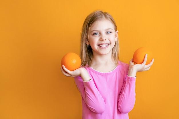 Słodkie dziecko 8 lat na pomarańczowej ścianie, ładna blondynka uśmiecha się z apelinami w dłoniach